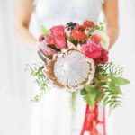 Krystal carried roses, ranunculus, ferns and one showstopping king protea wedding bouquet