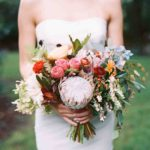 Protea, delphiniums, astrantia, leucadendrons, and rose hips wedding bouquet