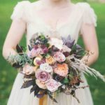 astilbes, maple leaves, dahlias, rice flowers, roses, baby artichokes, hypericums, and snowberry wedding bouquet