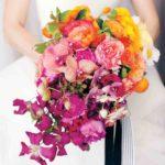 garden roses, tea roses, poppies, kumquats, tangerines, Meyer lemons, ranunculus, phalaenopsis orchids, peonies, blackberries, clematis, and sweet peas wedding bouquet