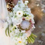 king proteas, sweet peas, ranunculus, veronicas, poppies, and garden spray roses wedding bouquet