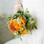 orange ranunculus, seeded eucalyptus, astrantia and sprigs of sage wedding bouquet