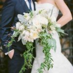 seasonal roses, dusty miller, astrantia, jasmine vines, and protea wedding bouquet