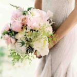 white and Pillow Talk peonies, garden roses, veronica, lady's-mantle, scabiosa, and peppermint geraniums wedding bouquet