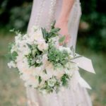 white peonies, garden roses, ranunculus, parrot tulips, sweet peas, hellebores, and trailing greenery wedding bouquet